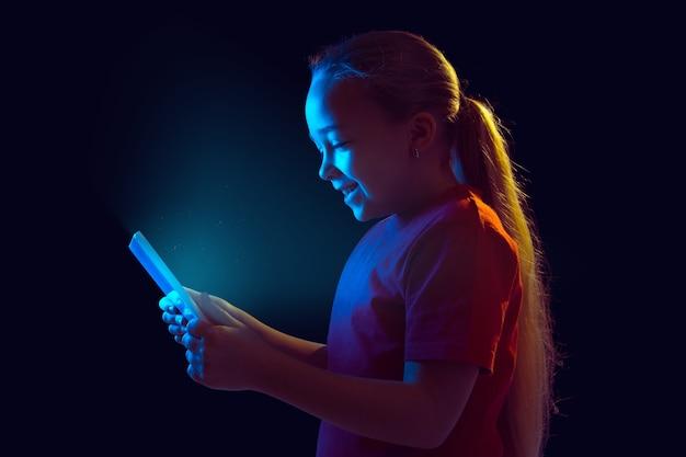 Sorridente. retrato da menina caucasiana isolado na parede escura em luz de néon. bela modelo feminino usando tablet. conceito de emoções humanas, expressão facial, vendas, anúncio, tecnologia moderna, gadgets.