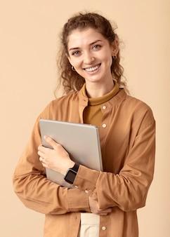 Sorridente senhora de cabelos cacheados segurando um laptop