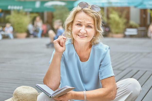 Sorridente senhora idosa branca ativa de cerca de 62 anos está sentada em um parque público e lendo um livro.