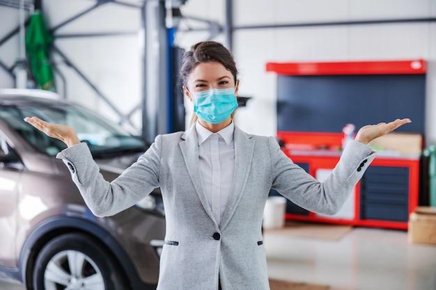 Sorridente, simpática vendedor de automóveis com máscara facial em pé na garagem do salão de automóveis e mostrando ao redor da garagem. o carro está pronto e consertado.