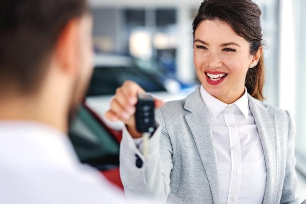 Sorridente, simpático vendedor de carros em pé no salão de carros com um cliente e entregando-lhe as chaves do carro mais vendido.