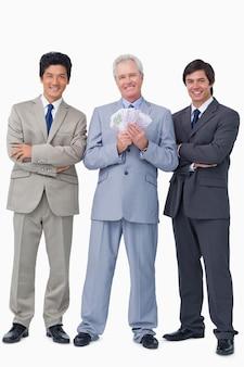 Sorridente vendedor sênior com dinheiro e funcionários