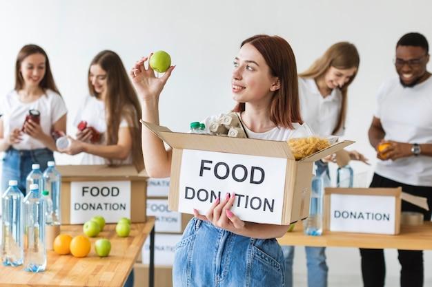 Sorridente voluntária segurando uma caixa de doação de alimentos com uma maçã
