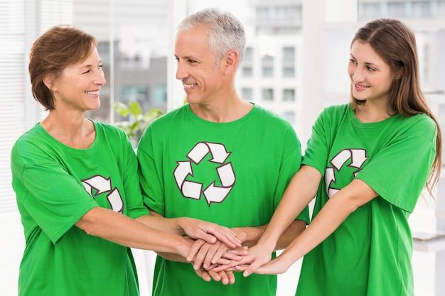 Sorridentes colegas de espírito ecológico colocando as mãos juntas