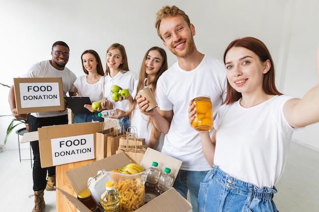 Sorridentes voluntários tirando selfie juntos enquanto preparam a comida para doação