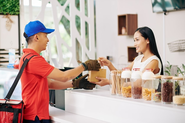 Sorrindo, a dona de uma pequena cafeteria dando um pedido embalado ao entregador