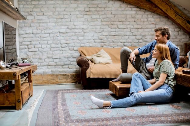 Sorrindo adorável casal jovem relaxando e assistindo tv em casa