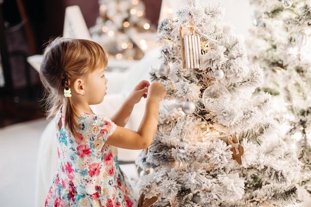 Sorrindo adorável menina vestido bonito com muitos presentes de natal