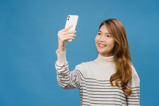 Sorrindo adorável mulher asiática fazendo foto de selfie no telefone inteligente com expressão positiva em roupas casuais e ficar isolado na parede azul
