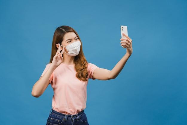 Sorrindo adorável mulher asiática usando máscara médica fazendo selfie foto no telefone inteligente com expressão positiva em roupas casuais e suporte isolado na parede azul