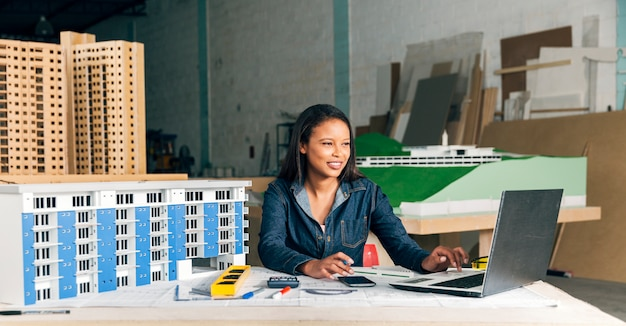 Sorrindo, africano-americano, senhora, com, laptop, e, modelo, de, predios