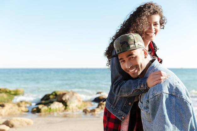 Sorrindo africano casal apaixonado caminhando ao ar livre na praia