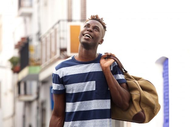 Sorrindo africano viajante masculino ao ar livre na rua com saco