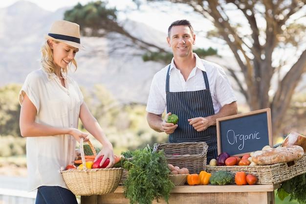 Sorrindo agricultor vendendo pimentões vermelhos e verdes