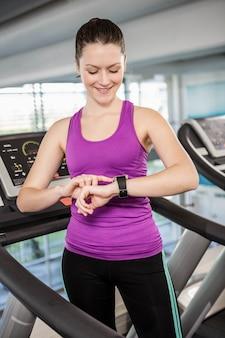 Sorrindo, ajuste, mulher, usando, smartwatch, ligado, treadmill, em, a, ginásio