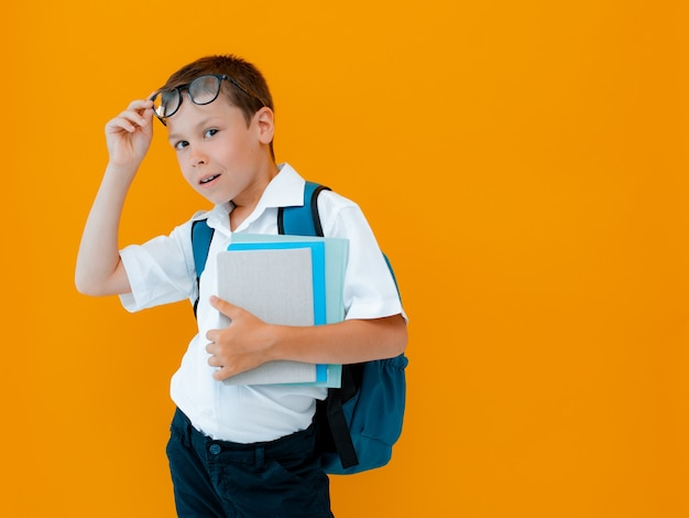 Sorrindo alegre estudante contra fundo amarelo. uma criança com uma mochila, livros e cadernos. o menino está pronto para estudar. de volta à escola.