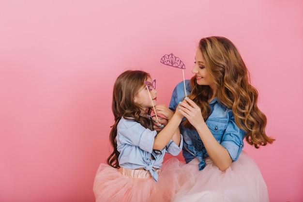 Sorrindo alegre jovem mãe olhando com amor para sua filha de cabelos compridos usando máscara roxa de carnaval. adorável menina em camisa jeans se divertindo e brincando com a mãe, segurando as mãos dela