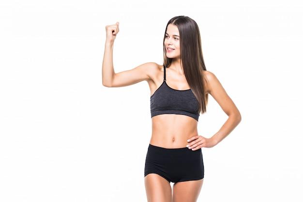 Sorrindo alegremente desportiva mulher demonstrando bíceps, isolado no branco
