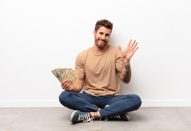Sorrindo alegremente e alegremente, acenando com a mão, dando as boas-vindas e cumprimentando-o ou dizendo adeus segurando as notas de dólar