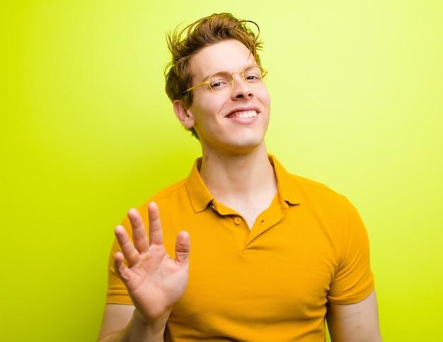 Sorrindo alegremente e alegremente, acenando com a mão, dando as boas-vindas e cumprimentando-o ou dizendo adeus