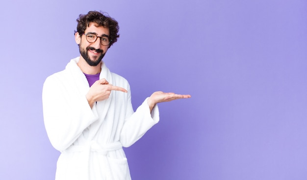 Sorrindo alegremente e apontando para copiar o espaço na palma da mão, mostrando ou anunciando um objeto