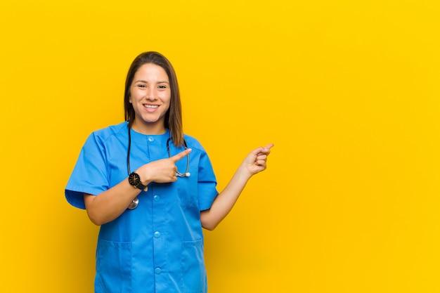 Sorrindo alegremente e apontando para o lado e para cima com as duas mãos, mostrando o objeto no espaço da cópia isolado contra a parede amarela