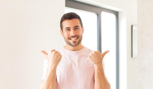 Sorrindo alegremente e parecendo feliz, sentindo-se despreocupado e positivo com ambos os polegares para cima