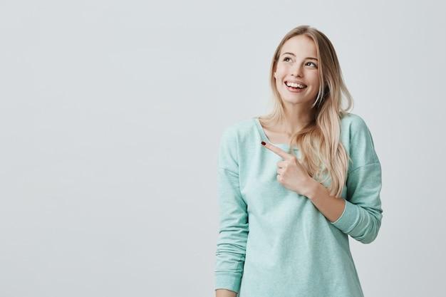 Sorrindo alegremente feminino com cabelo loiro, apontando os dedos indicadores, mostrando o espaço da cópia