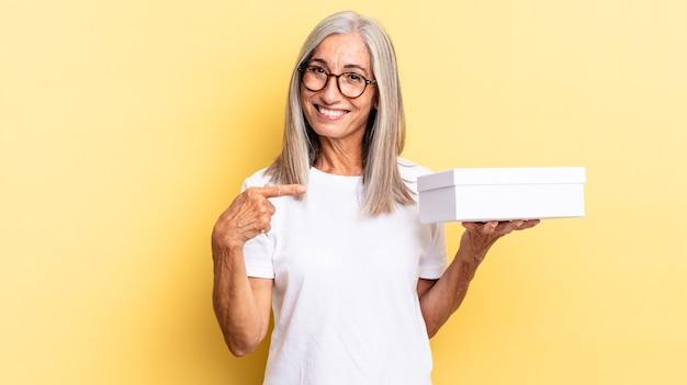 Sorrindo alegremente, sentindo-se feliz e apontando para o lado e para cima, mostrando o objeto no espaço da cópia e segurando uma caixa branca