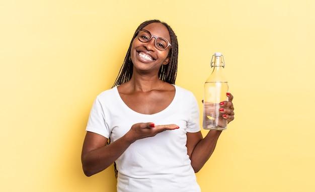 Sorrindo alegremente, sentindo-se feliz e mostrando um conceito no espaço da cópia com a palma da mão. conceito de garrafa de água