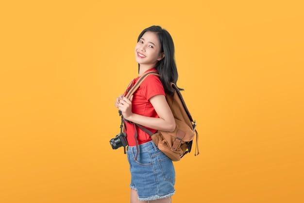 Sorrindo alegremente viajante de mulher asiática segurando a câmera e mochila