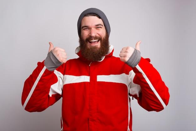 Sorrindo alpinista homem com barba, vestindo roupas de inverno e mostrando os polegares