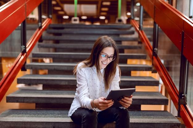 Sorrindo aluna com óculos e cabelo castanho, usando o tablet enquanto está sentado na escada.