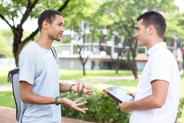 Sorrindo alunos do ensino médio se comunicando ao ar livre