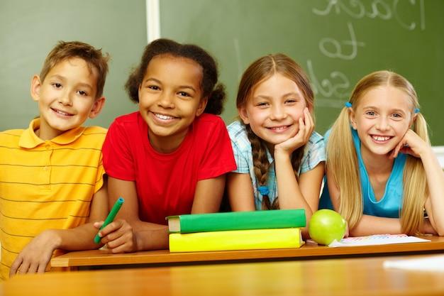 Sorrindo alunos do ensino primário que sentam-se na sala de aula