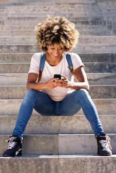 Sorrindo, americano africano, estudante universitário, sentar escada, com, telefone pilha