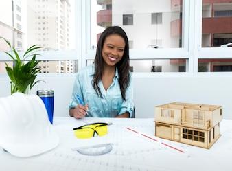 Sorrindo, americano africano, senhora, ligado, cadeira, com, caneta, perto, capacete segurança, e, modelo, de, casa, ligado, tabela