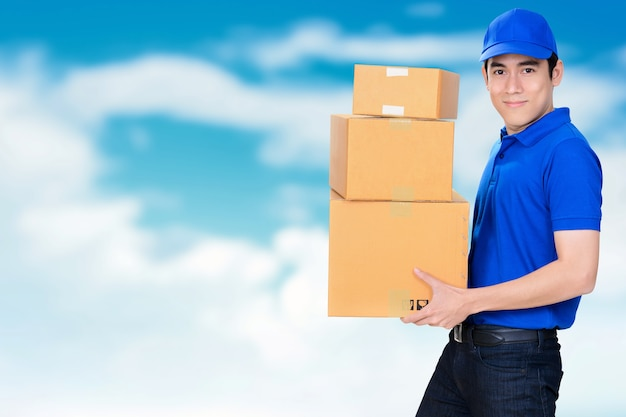 Sorrindo, amigo, entrega, homem, carregar, pacote, caixas, borrão, azul, céu, fundo