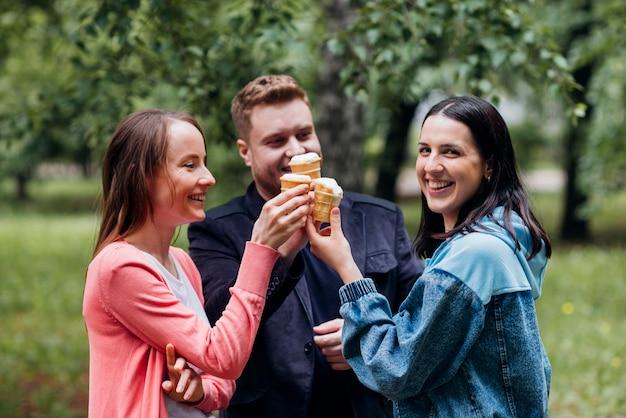 Sorrindo amigos a passar tempo juntos no parque comendo sorvete