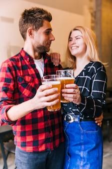 Sorrindo amigos brindando os copos de cerveja, olhando um para o outro