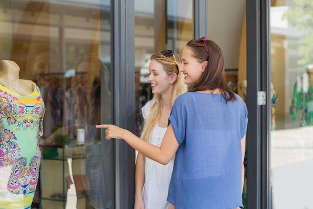 Sorrindo amigos dedo apontando um vestido