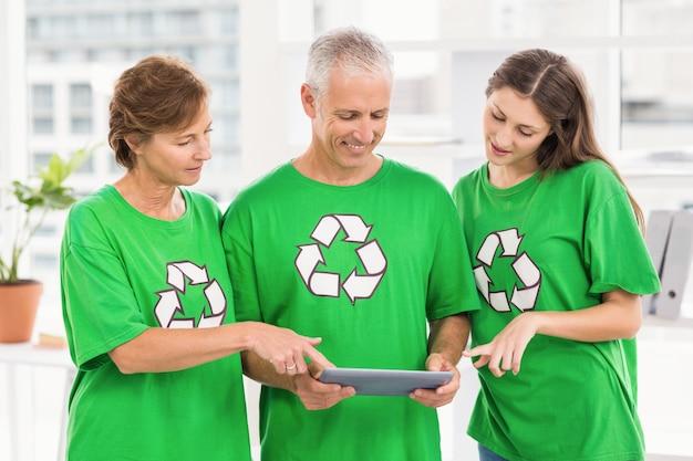 Sorrindo amigos ecológicos usando o tablet