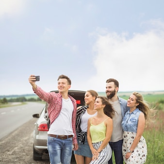 Sorrindo, amigos, ficar, perto, a, estacionado, car, levando, auto-retrato