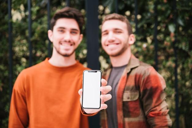 Sorrindo, amigos, mostrando, smartphone, para, câmera