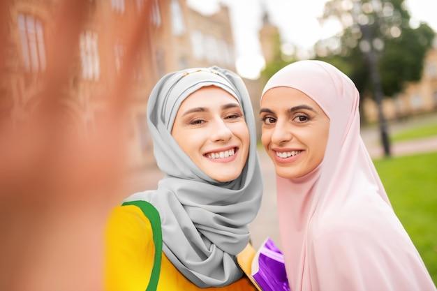 Sorrindo amplamente. alunos muçulmanos alegres usando hijabs e sorrindo amplamente