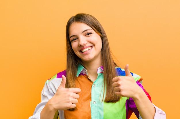 Sorrindo amplamente olhando feliz, positivo, confiante e bem-sucedido, com os dois polegares para cima