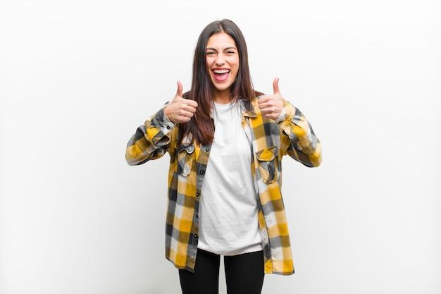 Sorrindo amplamente parecendo feliz, positivo, confiante e bem-sucedido, com ambos os polegares para cima