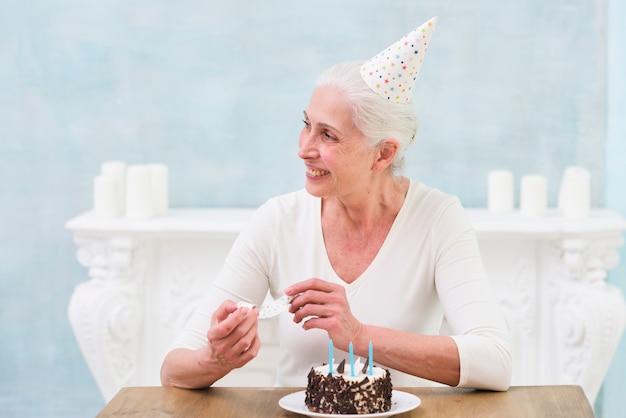 Sorrindo, aniversário sênior, mulher senta-se, perto, bolo, segurando, parte, chifre