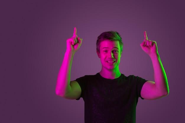 Sorrindo, apontando para cima. copyspace. retrato do homem caucasiano no fundo roxo do estúdio em luz de néon. lindo modelo masculino de camisa preta. conceito de emoções humanas, expressão facial, vendas, anúncio.