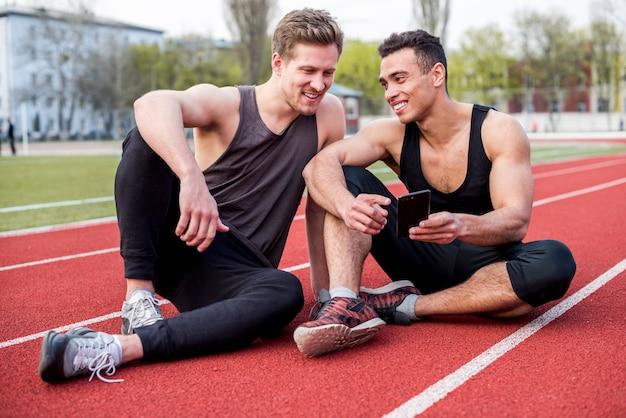 Sorrindo atleta do sexo masculino sentado na pista de corrida, mostrando o telefone celular para seu amigo